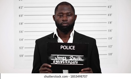 Mugshot of criminal afro-american businessman at police station. Afro broker arrested for bribery holding placard posing for mug shot with height chart on background
