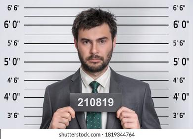 Mugshot of man in suit at police station - prisoner identification concept