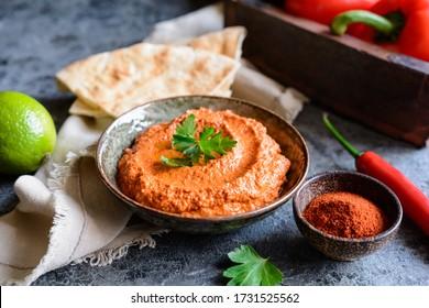 Muhammara, noyer sain et poivron rouge rôti, servi avec du pain plat dans un bol en céramique