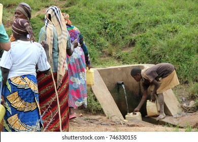 MUHANGA, RWANDA - CIRCA JULY 2016: In the village of Cyeza, a young Rwandan boy fetches drinking water from the well in his 2 10-liter yellow water containers while the women wait in line.