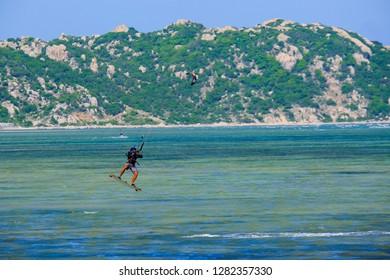Mui Ne, Vietnam - 11 2018: Kitesurfing, kiteboarding, kite surf. Extreme sport kitesurfing in tropical blue ocean beach. Stock photo image of professional kitesurfing on the waves of the beautiful sea