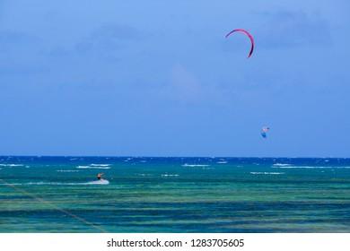 Mui Ne, Vietnam - 11 2018: Kitesurfing, kiteboarding, kite surf. Extreme sport kitesurfing in tropical blue ocean, clear beach. Stock photo image of kitesurfing on the waves of the beautiful sea