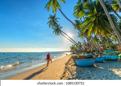 Mui Ne, Vietnam - April 21, 2018: The man alone go to end of tropical beach with coconut palm trees as sun gradually create beautiful setting for weekend guests at paradise beach in Mui Ne, Vietnam