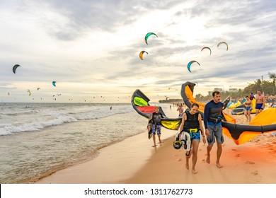 MUI NE, VIETNAM - December 29, 2018: People practicing kitesurf on the beach of Phan Thiet town (Mui Ne), Vietnam. Kitesurfing is a surface water sport