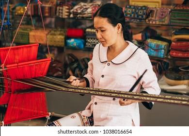 MUI NE, VIETNAM - MARCH 6, 2017: Woman Asian weaver working on a traditional loom for yarn silk workshop