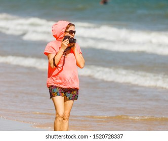 MUINE, VIETNAM - JANUARY 31, 2014: Girl photographer at the sea in Mui Ne, Vietnam. Girl removes kitesurfers athletes