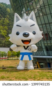 Muju,South Korea; May 1, 2019:Statue of  Taekwondowon mascot Jin Jin wearing uniform with red belt standing in front of competition arena.