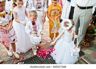 Mukyluntsi , Ukraine - 26 june, 2016: First holy communion. A little girl dressed as an angel sprinkles rose petals