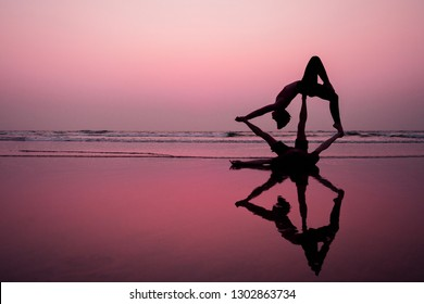 muladhara swadhisthana manipula tantra yoga on the beach man and woman meditates sitting on the sand by the sea at sunset romantic Valentine's Day.couple practicing yoga steam