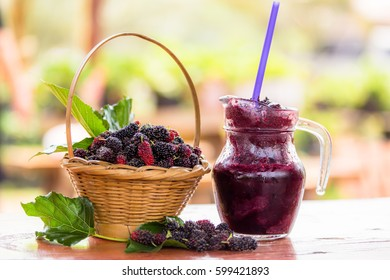 Mulberries and mulberries juice on wood table and soft background.