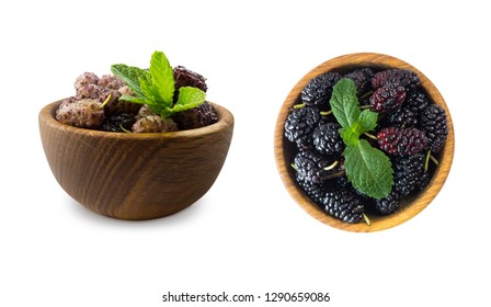 Mulberries in a wooden bowl with copy space for text. Black and purple mulberry on white background. Ripe and tasty mulberry isolated on white background. Top view.