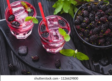 mulberry cocktail with ice and fresh mint on a black wooden table. refreshing summer drink