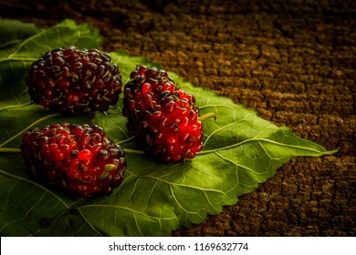 Mulberry and leaves on a wooden background