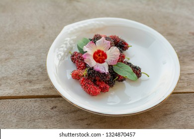 Mulberry  in a white plate on a wooden floor
