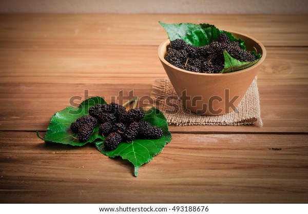 mulberry in wooden bowl and green leaf, some time call raspberry or blackberry which is fruit that is high vitamin C