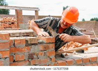 MULCHYCI, Rivne / UKRAINE - JUNE 22 2011: Man puts a brick in the construction