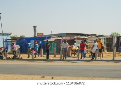 Muldersdrift, Johannesburg / South Africa - September 16 2018: African people standing on the pavement waiting for transport with blue sky