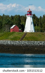 Mulholland lighthouse, a Canadian beacon, sits atop a hill by the rocky coast of Campobello Island during low tide on a summer day.