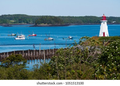 Mulholland Point lighthouse tower overlooks harbor with fishing boats nearby in summer. The wooden beacon lies on Campobello Island in Canada.