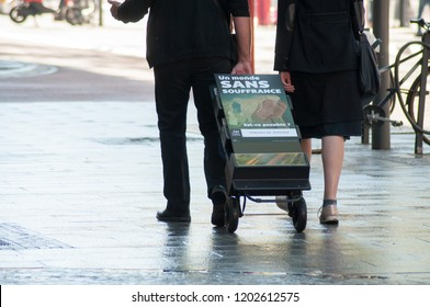 """Mulhouse - France - 14 October 2018 - Jehovah witnesses walking in the street with french text  on trolley """"Un onde sans souffrance"""" traduction in english : (a world without suffering)"""