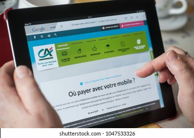 Mulhouse - France - 16 March 2018 - closeup of woman hands on the credit agricole home page of web site on tablet