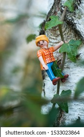 Mulhouse - France - 16 October 2019 - Closeup of Playmobil figurine climbing on tree trunk in outdoor