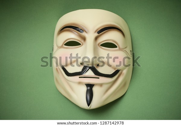 Mulhouse - France - 17 January 2019 - Vendetta mask on green paper background . This mask is a well-known symbol for the online hacktivist group Anonymous