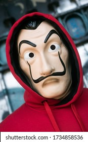 """Mulhouse - France - 18 May 2020 - fan of """"La casa de papel"""" (paper house) in english the serie TV on Netflix, standing with red sweat shirt costume and Salvador Dali mask in outdoor"""