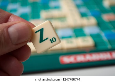 Mulhouse - France - 2 December 2018 - Closeup of plastic letters Z in hand on Scrabble board game
