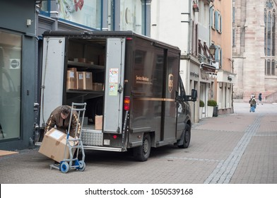 Mulhouse - France - 20 March 2018 - UPS delivery worker unloading packages from his truck in the street