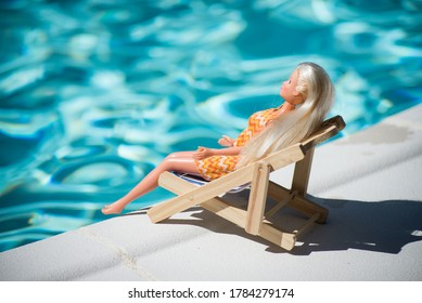 Mulhouse - France - 25 July 2020 - Portrait of Barbie doll lying in border the swimming pool in a wooden chair