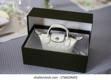 Mulhouse - France - 28 june 2020 - Closeup of white mini handbag by Longchamp in a luxury carton box on a table