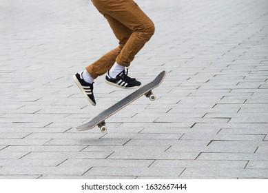 Mulhouse - France - 31 January 2020 - Closeup of skater legs wearing black sneakers by Adidas  jumping with skate board in the street