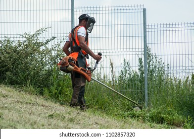 Mulhouse - France - 31 May 2018 - gardener with Brush cutter in a Sloping slope