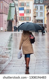 Mulhouse - France - 8 February 2019 - portrait of woman with grey umbrella in pedestrian street in the city