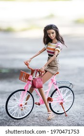 Mulhouse - France - 8 May 2021 - Portrait of brunette Barbie doll wearing a brown mini skirt on pink bicycle in the street