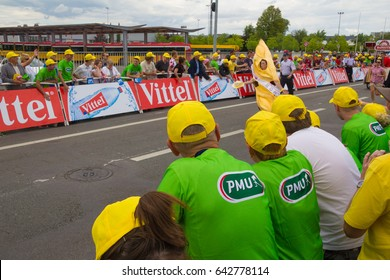 MULHOUSE, FRANCE JULY 13 2014: lots of yellow caps and green PMU shirts and a man in a banana costume