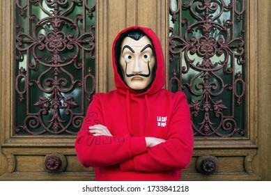 """Mulhouse -  France - May 17 2020 : fan of the serie tv """"La casa de papel' (paper house) traduction in english on Netflix standing with red sweat shirt costume and Salvador Dali mask in outdoor"""