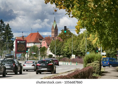 Mulhouse, France - September 15, 2017: road to Lutterbach with pointer on billboard. Street with Church and historic building, city view