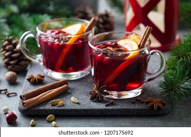 Mulled red wine with spices. Christmas decoration. Grey stone background. Close up.