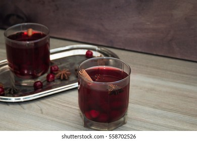 mulled wine with cherries, cinnamon and star anise in a glass on vintage silver tray