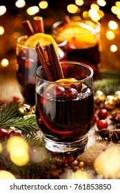 Mulled wine, Christmas hot drink with addition aromatic spices, citrus fruit and cranberries on a wooden rustic table
