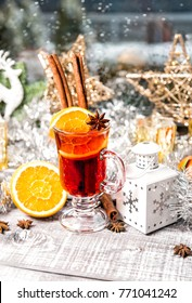 Mulled wine and Christmas window decoration. Winter cocktail drink with fruits and spices