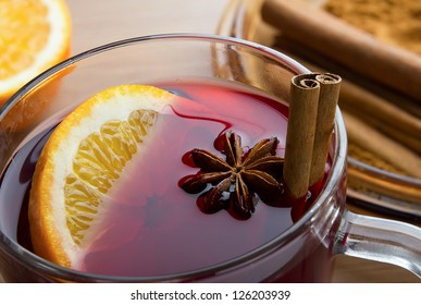 Mulled wine flavored with spices in glass and oranges
