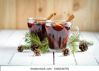 Mulled wine in glass glasses with apples, orange, cinnamon and star anise. Hot christmas drink on light background with spruce branch.