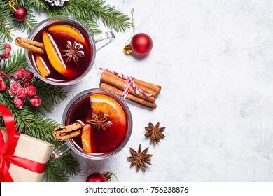 Mulled wine in glass mug with spices. Christmas hot drink on gray stone table. Top view.
