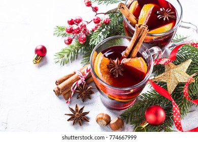 Mulled wine in glass mug with spices. Christmas hot drink on gray stone table with copy space.