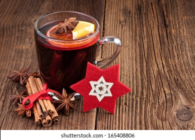 Mulled wine in a glass on old wooden background