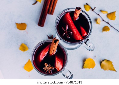 Mulled wine hot fall drink with citrus, apple and spices in glass on blue stone concrete background. Autumn hot drink. Fall autumn yellow leaves. Top view