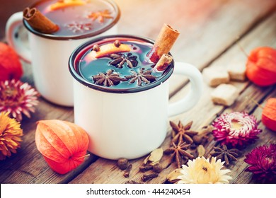 Mulled wine in mugs, spice and dry flowers. Autumn still life.